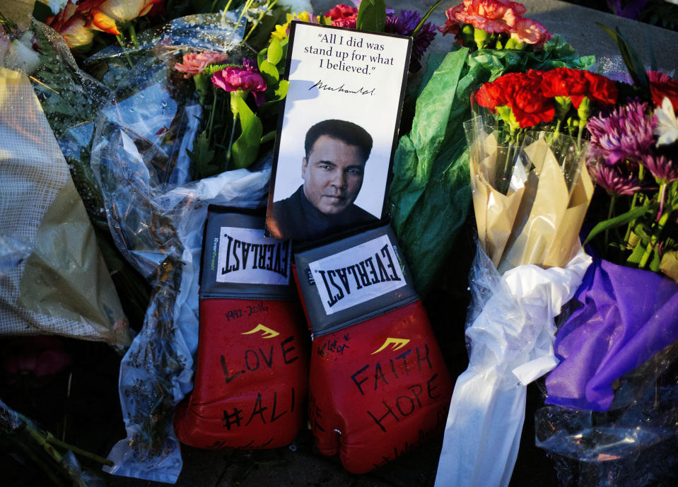 """FILE - Boxing gloves and a message sit among flowers at a makeshift memorial to Muhammad Ali at the Muhammad Ali Center in Louisville, ky., in this Saturday, June 4, 2016, file photo. A new documentary looks at the city that raised Muhammad Ali, Louisville, Kentucky, and the week of his funeral, when the community came together to celebrate the legacy of """"The Greatest."""" (AP Photo/David Goldman, File)"""