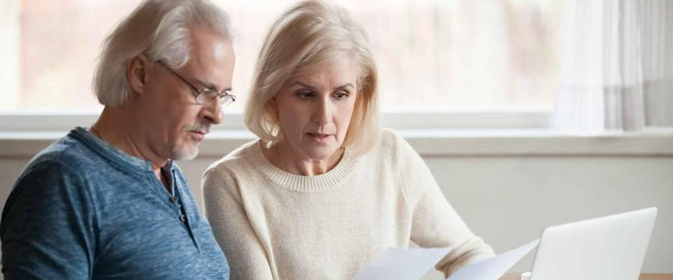 Serious senior couple looking at bills while sitting in front of laptop