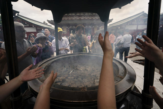 A group of visitors engulf themselves with smoke as they gather around a incense burner at Sensoji Temple in the Taito district of Tokyo, June 3, 2019. It is believed that the smoke carries healing powers and purifies the body and mind. (AP Photo/Jae C. Hong)
