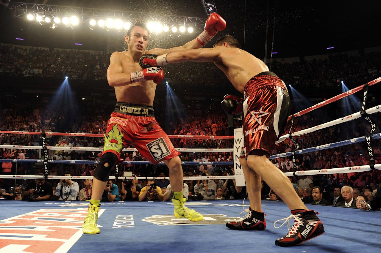 LAS VEGAS, NV - SEPTEMBER 15:  Julio Cesar Chavez Jr. (L) takes a left from Sergio Martinez in the 12th round of their WBC middleweight title fight at the Thomas & Mack Center on September 15, 2012 in Las Vegas, Nevada.  (Photo by Jeff Bottari/Getty Images)