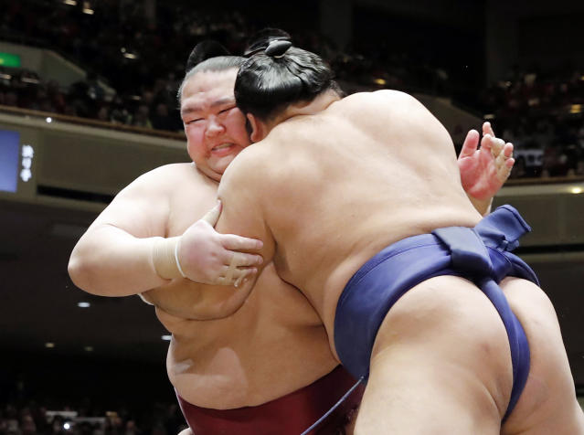 In this Tuesday, Jan. 15, 2019, photo, grand champion Kisenosato, left, is pushed by Tochiozan at the New Year Grand Sumo Tournament in Tokyo. Kisenosato, the only Japanese wrestler at sumo's highest rank, has decided to retire after three straight losses at the tournament. (Kyodo News via AP)