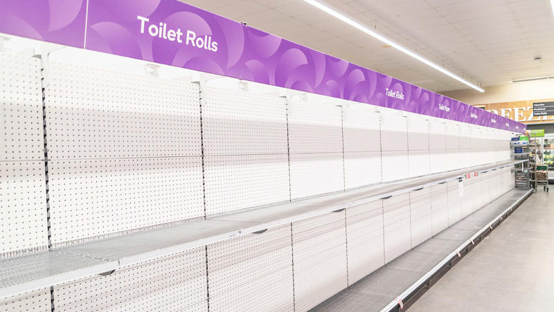 An empty row of toilet paper rolls in a supermarket.
