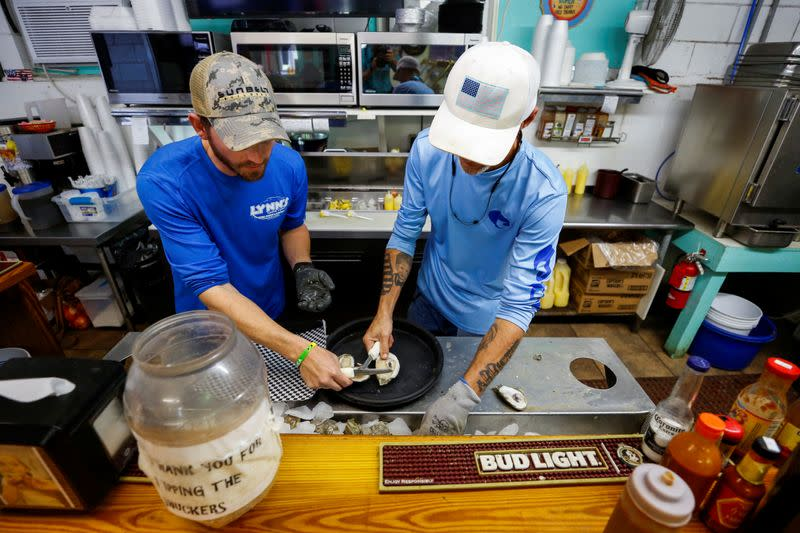 Brandon Martina and Michael Braswell of Lynn's Quality Oysters shuck oysters from Texas for waiting diners at the restaurant in Eastpoint, Florida