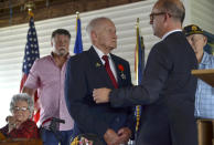 Consul General of France to the Midwest Guillaume Lacroix, right, stands by WWII veteran Jimmie H. Royer to hug after Lacroix awarded Royer France's Legion of Honor during a ceremony at VFW Post 346 in Terre Haute, Ind., Sunday, Sept. 29, 2019. The 94-year-old World War II veteran from western Indiana received the medal Sunday for his wartime service. (Austen Leake/The Tribune-Star via AP)