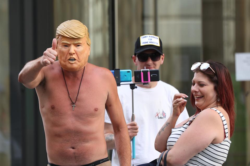 Supporters of Tommy Robinson, one wearing a Donald Trump mask, wait for his arrival at the Old Bailey in London where he is due to attend a committal hearing for alleged contempt of court.