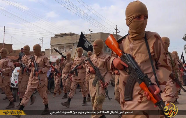 """FILE - In this file photo released on April 25, 2015, by a militant website, which has been verified and is consistent with other AP reporting, young boys known as the """"caliphate cubs"""" hold their rifles as they parade after graduating from a religious school, in Tal Afar, near Mosul city, north Iraq. The Arabic words, center, read: """"A parade of caliphate cubs after their graduation from a religious school."""" (Militant website via AP, File)"""