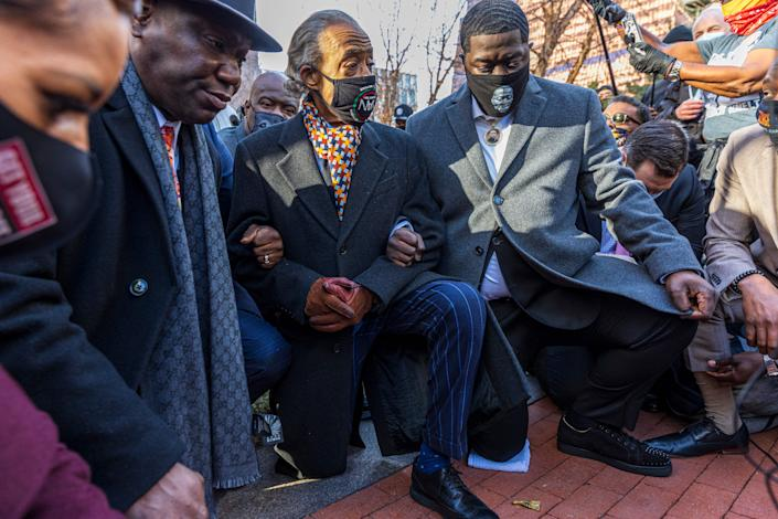 Attorney Benjain Crump (left), the Rev. Al Sharpton and George Floyd's family members kneel outside the courthouse on the opening day of the trial of former Minneapolis police officer Derek Chauvin Monday. (Kerem Yucel/AFP via Getty Images)