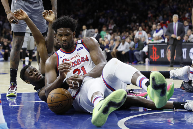 Philadelphia 76ers' Joel Embiid, center, battle for a loose ball with Brooklyn Nets' Caris LeVert during overtime in an NBA basketball game, Thursday, Feb. 20, 2020, in Philadelphia. Philadelphia won 112-104. (AP Photo/Matt Slocum)