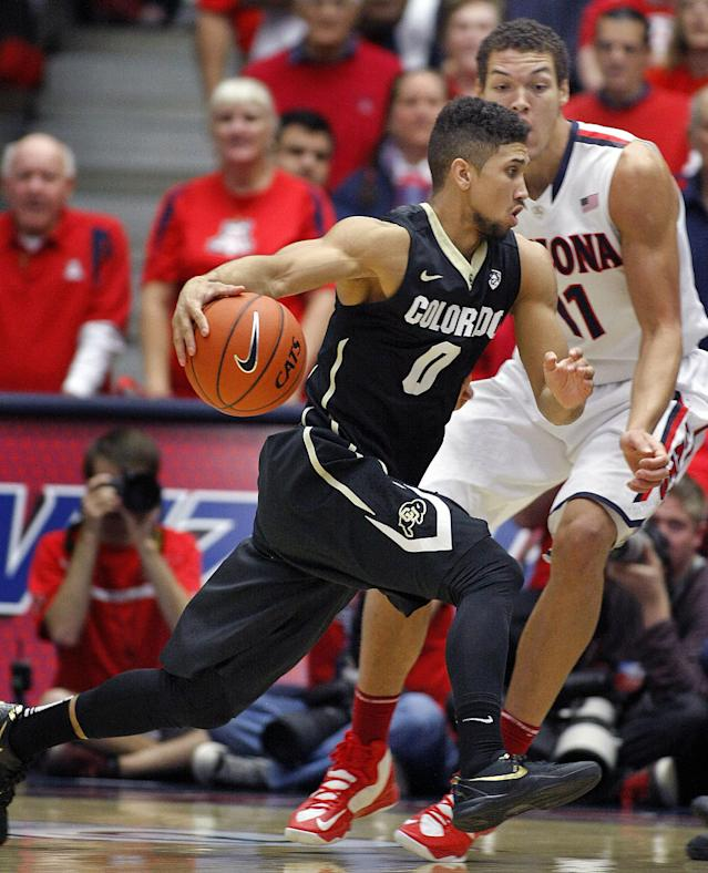 Colorado's Askia Booker (0) drives pass the attempted defense of Arizona's Aaron Gordon (11) in the first half of an NCAA college basketball game, Thursday, Jan. 23, 2014 in Tucson, Ariz. (AP Photo/John Miller)