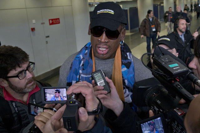 Former NBA star Dennis Rodman, center, arrives at the capital airport for a flight to North Korea, in Beijing, China, Thursday, Dec. 19, 2013. Rodman is flying to North Korea to help train the national team and renew his friendship with the North's young leader Kim Jong Un, a visit unaffected by the recent execution of Kim's uncle in a dramatic political purge. (AP Photo/Ng Han Guan)