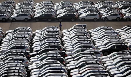 FILE PHOTO: A worker is seen among newly manufactured cars awaiting export at port in Yokohama