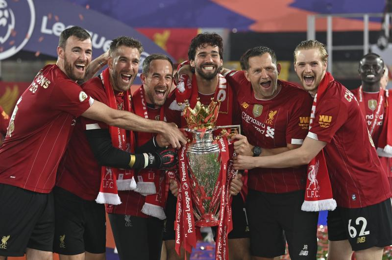 Alisson, center, holds the Premier League trophy surrounds by smiling Liverpool teammates and staff.