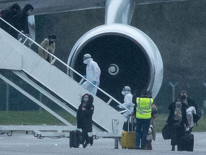 People in protective suits help passengers get off a plane with 150 British people evacuated from Wuhan, China, on February 9, 2020, in Brize Norton, England, due to the coronavirus outbreak.