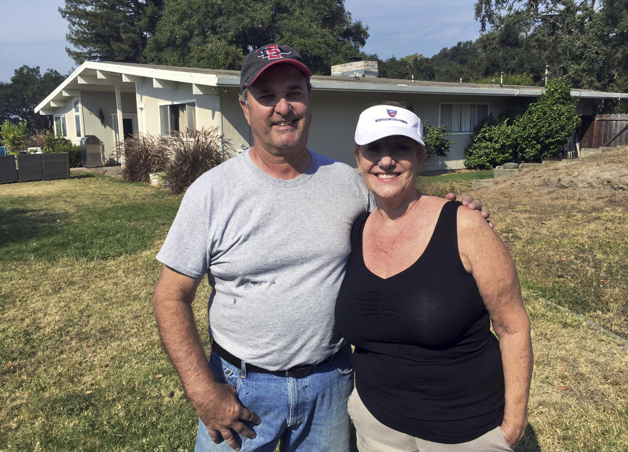 Tom and Catherine Andrews pose at their home in Santa Rosa, Calif., Monday, Oct. 16, 2017. They live on the edge of devastation. On one side of their mid-century style home, the deadly wildfires that ravaged parts of Northern California for more than a week wiped away the houses of neighbors they have known as long as two decades. On the other side, were those like the Andrews, who were spared. (AP Photo/Terry Chea)