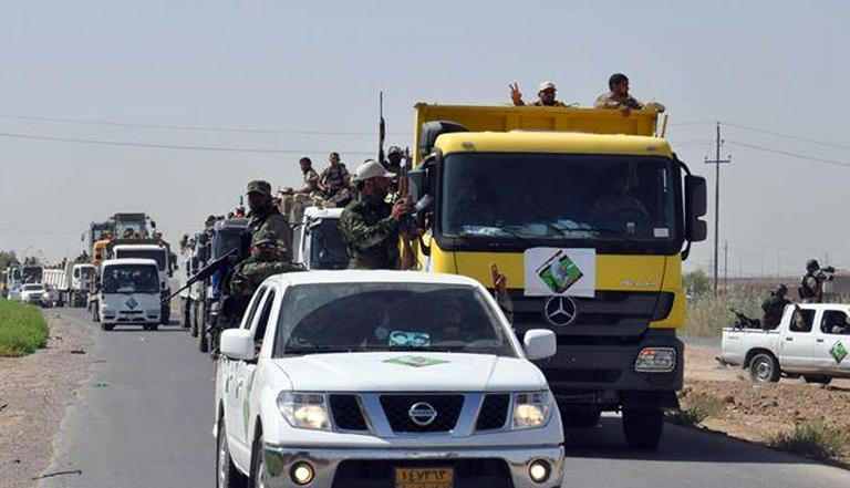 Iraqi forces and mainly Shiite Muslim volunteers arrive in the predominantly-Sunni Muslim city of Samarra on July 2, 2014