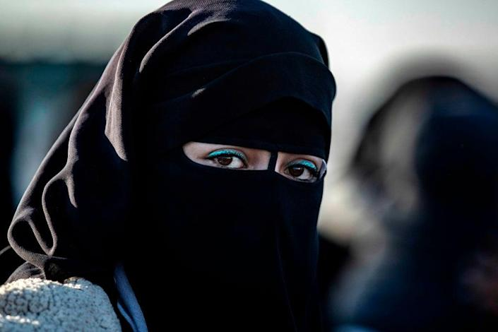 A Syrian woman waits to leave the Kurdish-run al-Hol camp holding relatives of alleged Islamic State group fighter (AFP via Getty Images)