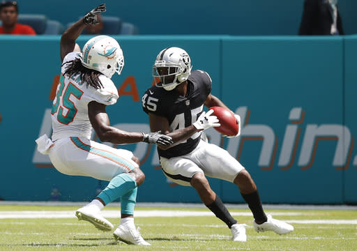 Oakland Raiders defensive back Dominique Rodgers-Cromartie (45) attempts to avoid Miami Dolphins defensive back Walt Aikens (35) as he returns a punt during the first half of an NFL football game, Sunday, Sept. 23, 2018, in Miami Gardens, Fla. (AP Photo/Brynn Anderson)