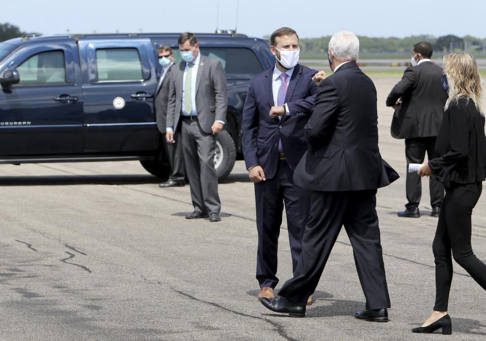 Florida Representative Chris Sprowls, center, offers an elbow bump to Vice President Mike Pence after he arrived in Tampa on Air Force Two with his daughter Charlotte, right, at Tampa International Airport on Wednesday Aug. 5, 2020, with plans to visit the Hilton Clearwater Beach Resort & Spa in Clearwater as part of his 'Faith in America' tour. (Douglas R. Clifford/Tampa Bay Times via AP)