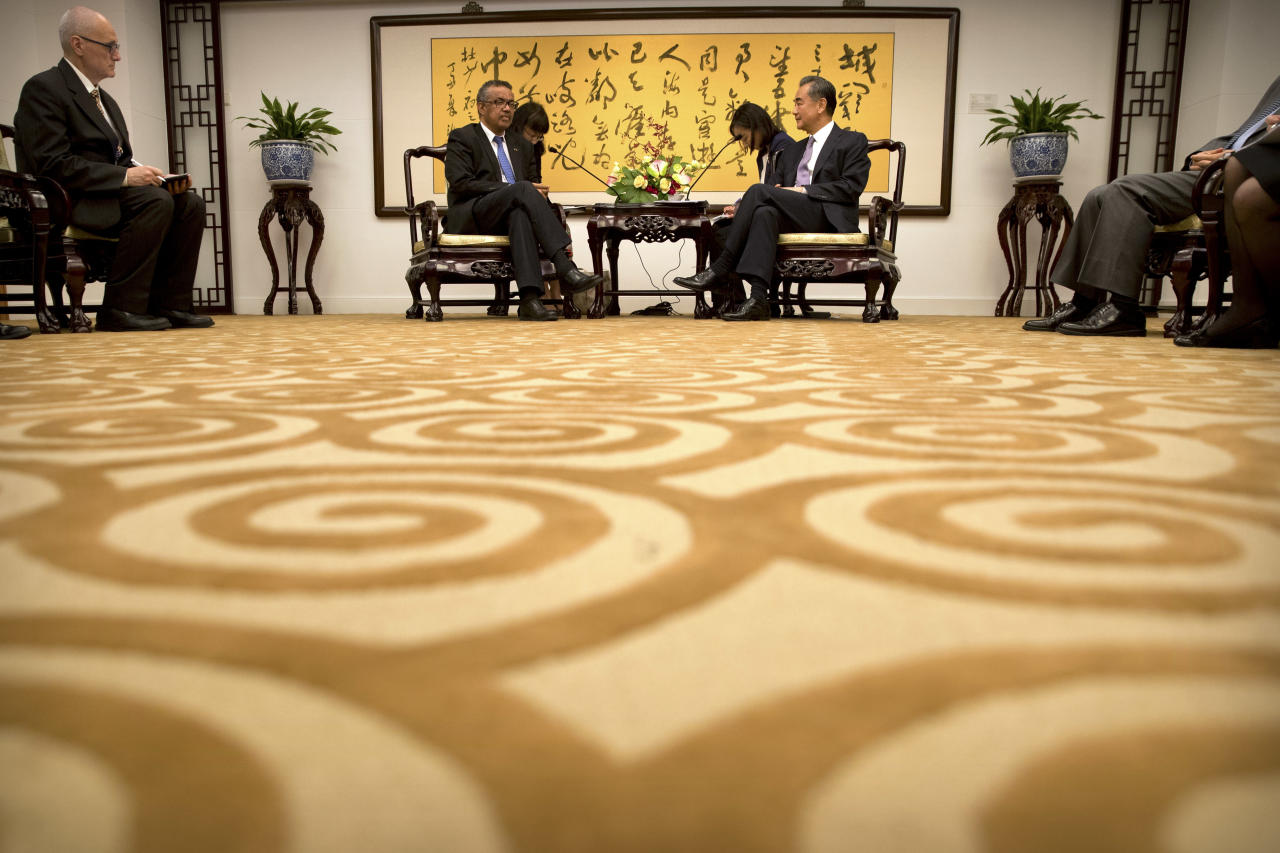 Tedros Adhanom Ghebreyesus, center left, director general of the World Health Organization (WHO), speaks during a meeting with Chinese Foreign Minister Wang Yi, center right, at the Ministry of Foreign Affairs in Beijing, Tuesday, July 17, 2018. (AP Photo/Mark Schiefelbein, Pool)