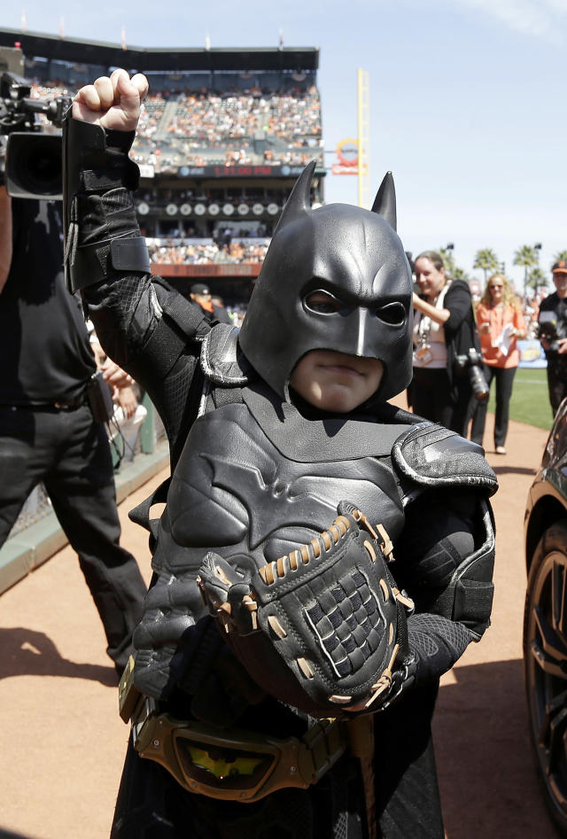 Miles Scott, dressed as Batkid, gestures after throwing the ceremonial first pitch before a home opener baseball game between the San Francisco Giants and the Arizona Diamondbacks in San Francisco, Tuesday, April 8, 2014. On Nov. 15, 2013, Scott, a Northern California boy with leukemia, fought villains and rescued a damsel in distress as a caped crusader through The Greater Bay Area Make-A-Wish Foundation. (AP Photo/Eric Risberg, Pool)