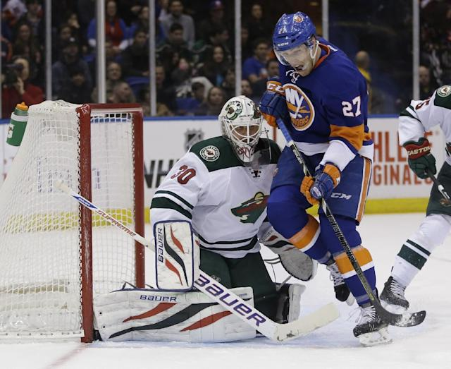 Minnesota Wild goalie Ilya Bryzgalov, left defends the goal while New York Islanders' Anders Lee skates past during the second period of the NHL hockey game, Tuesday, March 18, 2014, in Uniondale, New York. (AP Photo/Seth Wenig)