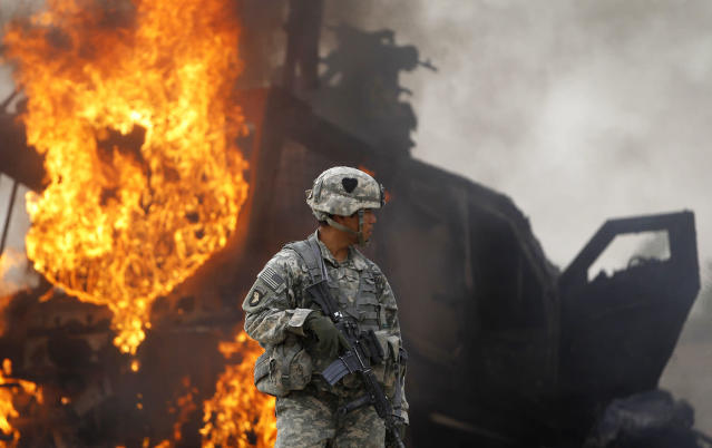 <p>Captain Melvin Cabebe with the US Army's 1-320 Field Artillery Regiment, 101st Airborne Division stands near a burning M-ATV armored vehicle after it struck an improvised explosive device (IED) near Combat Outpost Nolen in the Arghandab Valley north of Kandahar, on July 23, 2010. (Photo: Bob Strong/Reuters) </p>