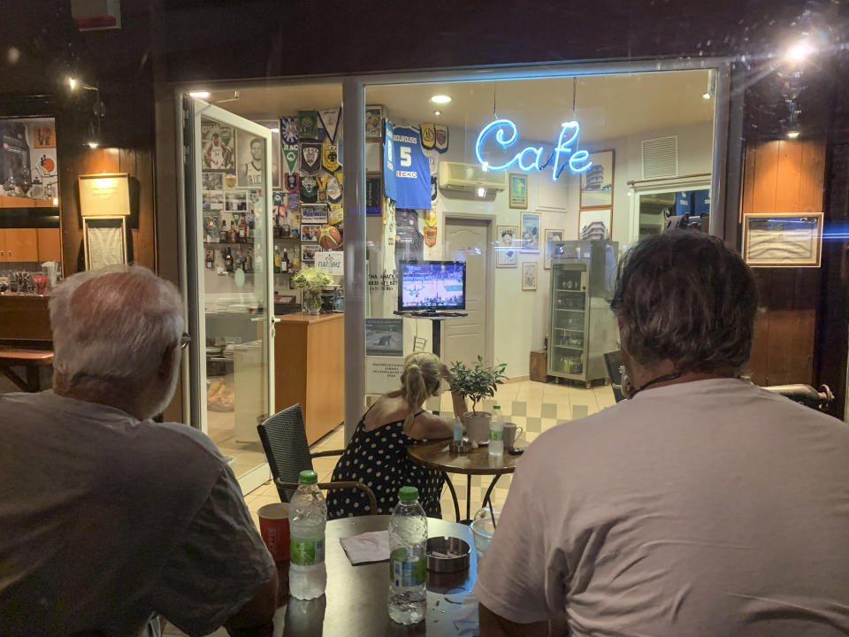 Fans watch Game 6 of the NBA Finals at a coffee shop, in the Sepolia district of Athens, Greece, on Wednesday, July 21, 2021. Milwaukee Bucks star Giannis Antetokounmpo grew up in Sepolia and used to stop at the coffee shop before basketball practice as a teenager. (AP Photo/Derek Gatopoulos)