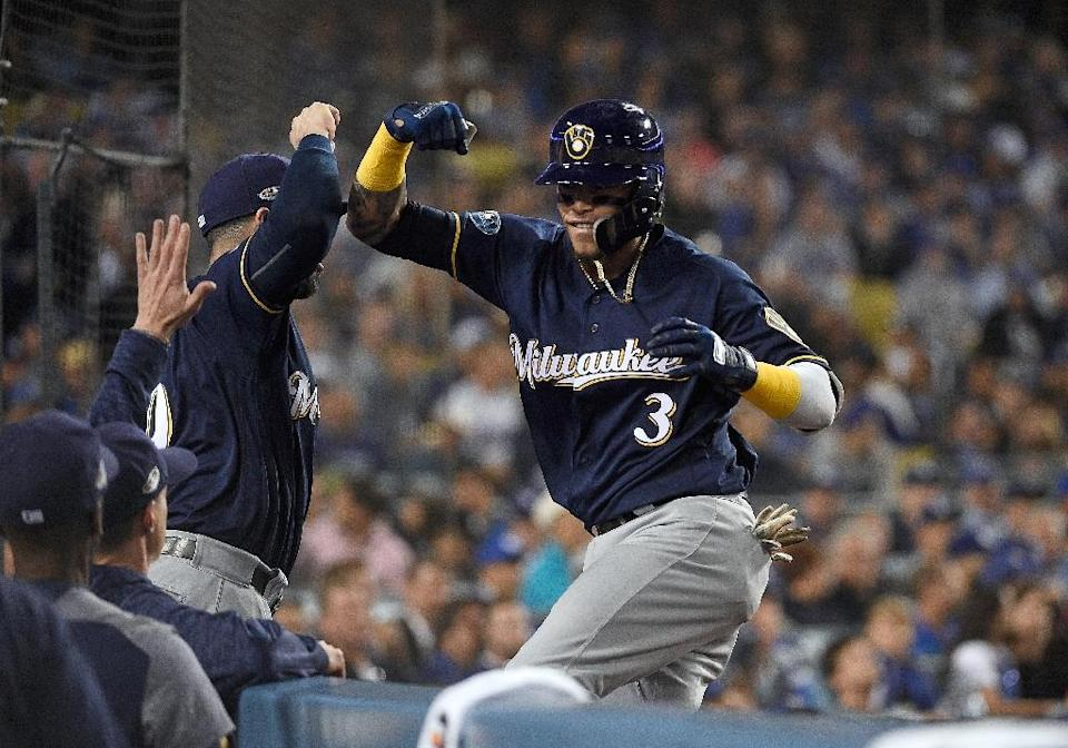 Milwaukee's Orlando Arcia celebrates with teammate Mike Moustakas after hitting a two-run homer in the Brewers' victory in Game 3 of the NLCS. (AP)