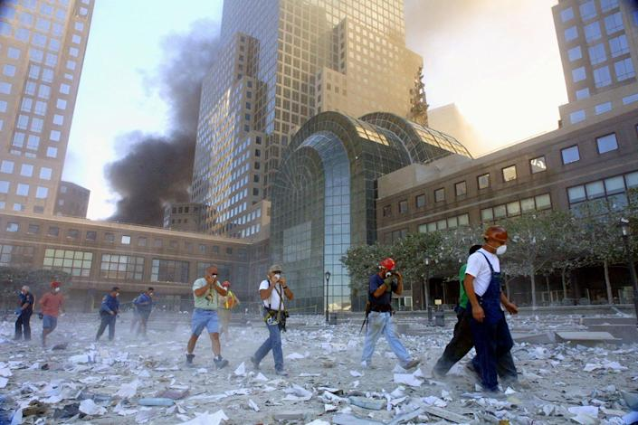 <p>People evacuate the World Trade Center after it was hit by two planes on Sept. 11, 2001, in New York City. (Photo: Mario Tama/Getty Images) </p>