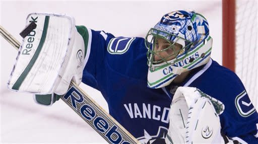 Vancouver Canucks goalie Roberto Luongo (1) makes a save against the Calgary Flames during third period NHL hockey action at Rogers Arena in Vancouver, British Columbia, Saturday, March, 31, 2012. (AP Photo/The Canadian Press, Jonathan Hayward)