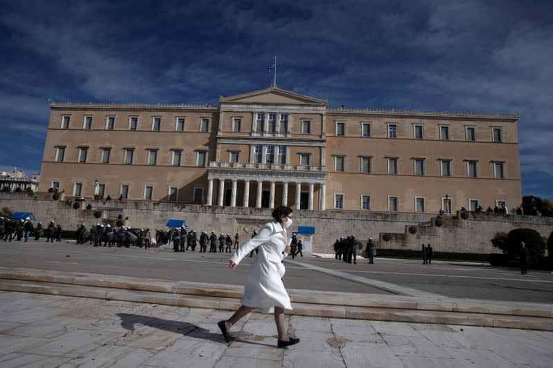 A woman wearing a protective face mask runs in front of the parliament building as Greek university students demonstrate against government plans to set up university police, amid the coronavirus disease (COVID-19) pandemic, in Athens