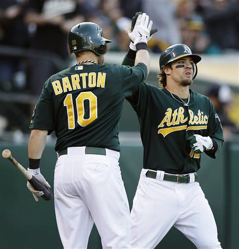 Oakland Athletics' Collin Cowgill, right, is congratulated by Daric Barton (10) after Cowgill scored against the Detroit Tigers during the seventh inning of a baseball game, Saturday, May 12, 2012, in Oakland, Calif. (AP Photo/Ben Margot)