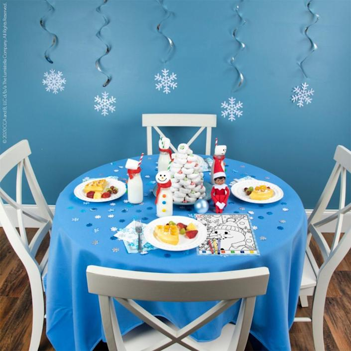 """<p>Plan a welcome back breakfast for your Scout Elf this year! It's the least you can do for such an honored guest. Snowflake napkins, a frosty blue tablecloth, and other cute details add to the fun.</p><p><strong>Get the tutorial at <a href=""""https://elfontheshelf.com/elf-ideas/snowy-welcome-back-breakfast/"""" rel=""""nofollow noopener"""" target=""""_blank"""" data-ylk=""""slk:Elf on the Shelf"""" class=""""link rapid-noclick-resp"""">Elf on the Shelf</a>.</strong></p>"""