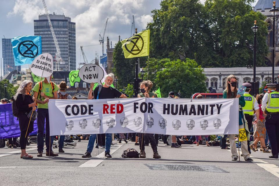 Demonstrators hold a banner which says Code Red For Humanity outside HM Revenue & Customs in Westminster during the protest. Extinction Rebellion staged protests at several locations in the capital on the second full day of their two-week campaign, Impossible Rebellion, calling on the UK Government to act meaningfully on the climate and ecological crisis. (Photo by Vuk Valcic / SOPA Images/Sipa USA)