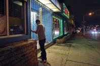 FILE - In this Nov. 12, 2020, file photo, on a mostly empty street, an employee of Justin's BBQ closes up for the night in Newark, N.J. An increasing number of governors and mayors are imposing restrictions ahead of Thanksgiving for fear that holiday travel and family gatherings will only worsen the record-breaking, coast-to-coast resurgence of the coronavirus. (AP Photo/Seth Wenig, File)