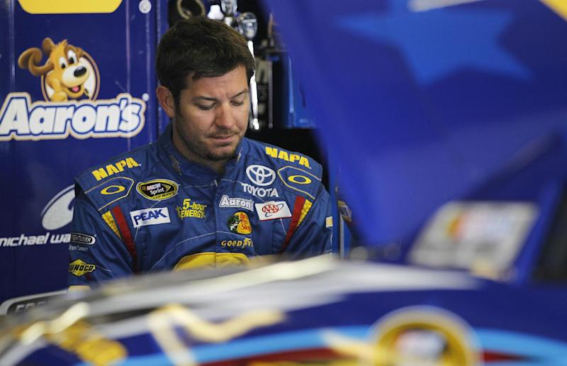 FILE - In this July 12, 2013 file photo, NASCAR driver Martin Truex Jr. reflects during practice at New Hampshire Motor Speedway in Loudon, N.H. NASCAR's investigation into Clint Bowyer's spin at Richmond ultimately uncovered a series of deliberate actions by Michael Waltrip Racing to alter the race results and the field for the Chase for the Sprint Cup championship. The sordid saga concluded Monday, Sept. 10, 2013, with a hefty penalty that saw Ryan Newman replace Martin Truex Jr. in the Chase as MWR was fined $300,000, and general manager Ty Norris received an indefinite suspension. (AP Photo/Cheryl Senter, File)