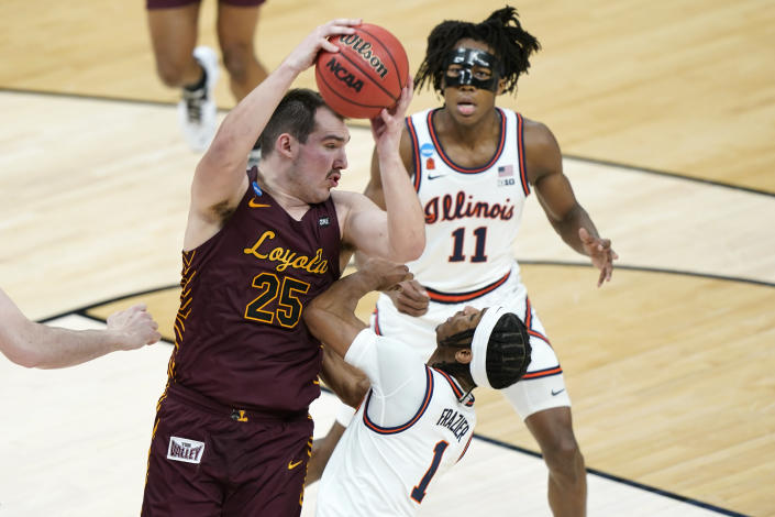Loyola of Chicago's Cameron Krutwig (25) grabs a rebound above Illinois' Trent Frazier (1) during the first half of a college basketball game in the second round of the NCAA tournament at Bankers Life Fieldhouse in Indianapolis Sunday, March 21, 2021. (AP Photo/Mark Humphrey)