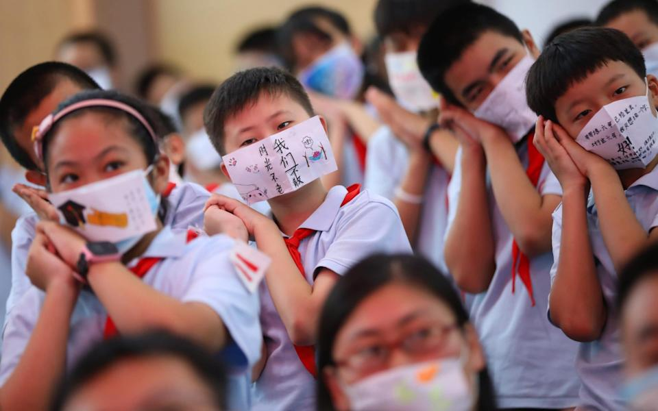Students wear face masks with blessing messages during a graduation ceremony at a primary school - China News Service