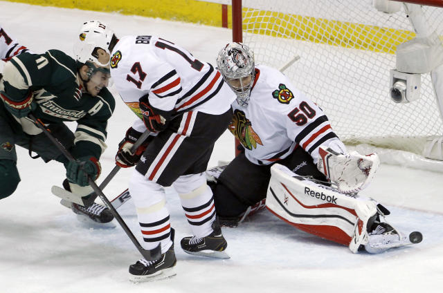 Chicago Blackhawks goalie Corey Crawford (50) deflects a shot in front of Blackhawks defenseman Sheldon Brookbank (17) and Minnesota Wild left wing Zach Parise (11) during the first period of Game 6 of an NHL hockey second-round playoff series in St. Paul, Minn., Tuesday, May 13, 2014. (AP Photo/Ann Heisenfelt)