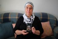 Syrian immigrant Hallak holds a phone with a picture of her dead son Ayham in Berlin
