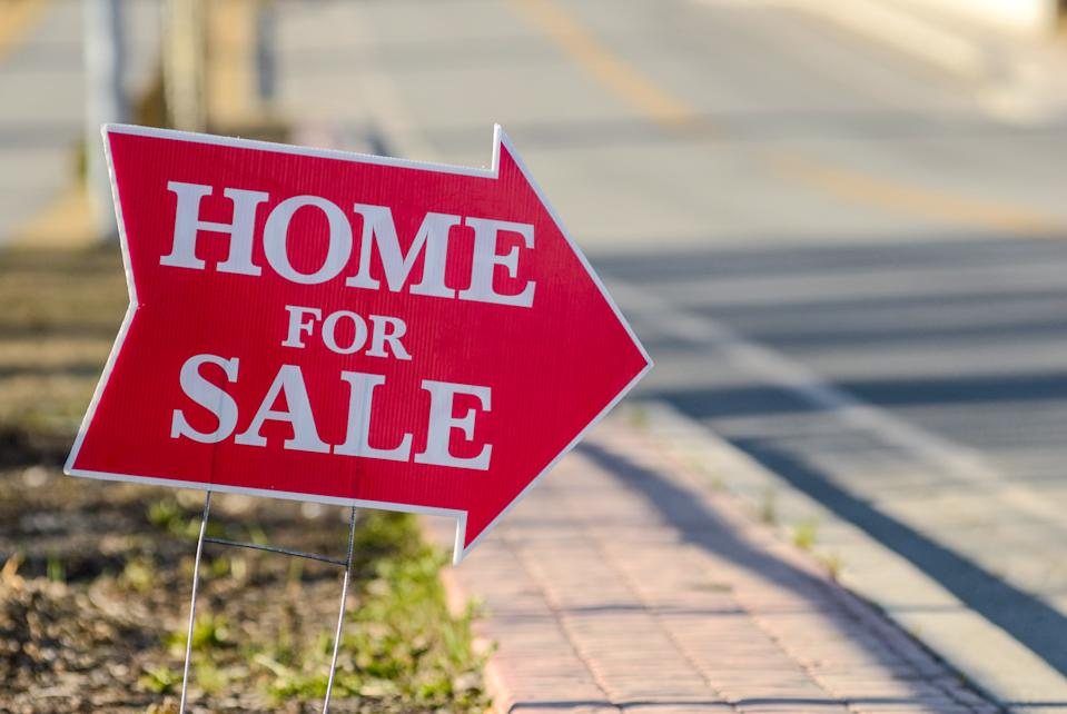 A home for sale sign pointing directing people to a house for sale