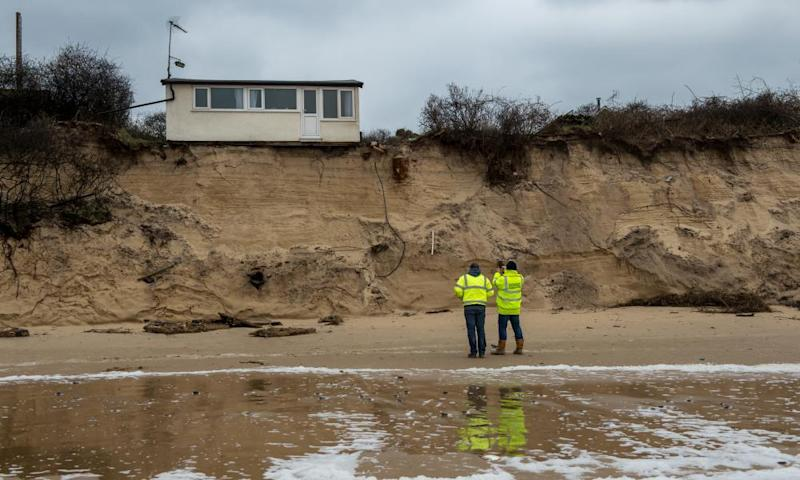 Building control surveyors on Hemsby beach in front of houses that have been evacuated.