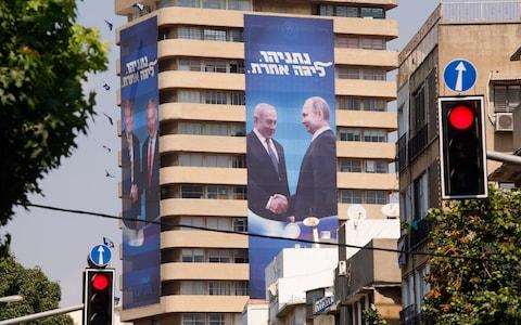 Political posters showing Netanyahu with Putin, right hang from the Likud Center in Tel Aviv - Credit: Kobi Wolf/Bloomberg