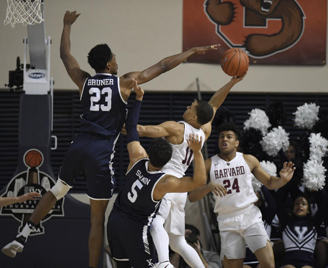 Harvard's Bryce Aiken (11) shoots as Yale's Jordan Bruner (23) and Yale's Azar Swain (5) defend during the first half of an NCAA college basketball game for the Ivy League championship at Yale University in New Haven, Conn., Sunday, March 17, 2019, in New Haven, Conn. (AP Photo/Jessica Hill)