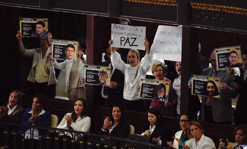 Lilian Tintori (C), wife of jailed opposition leader Leopoldo Lopez, and relatives of other jailed figures, hold signs during a session of the National Assembly in Caracas on February 4, 2016