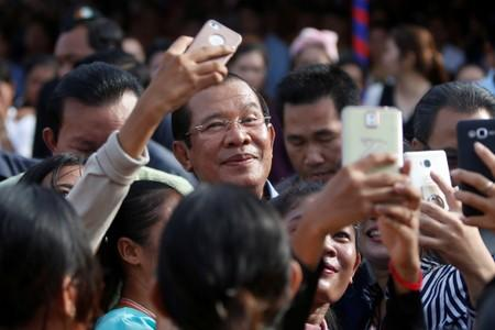 FILE PHOTO: Garment workers welcome Cambodia's Prime Minister Hun Sen during a rally in Kandal province