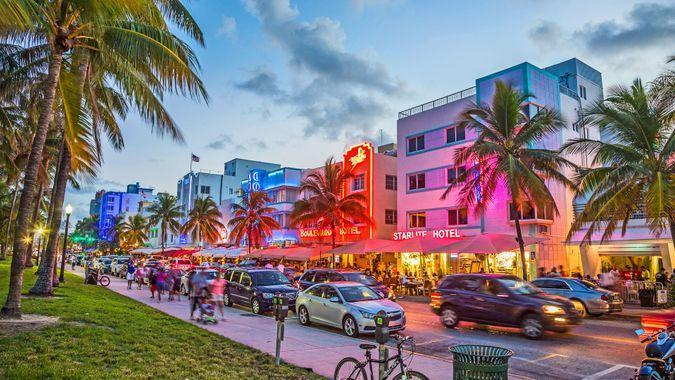 Miami, USA - August 23, 2014: people enjoy Palm trees and art deco hotels at Ocean Drive by night.