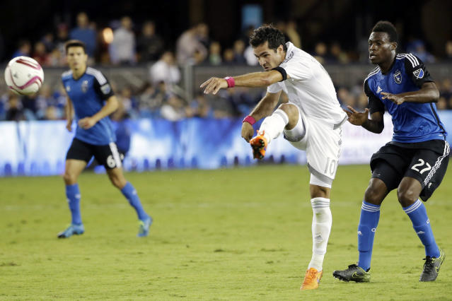 FILE - In this Oct. 16, 2015, file photo, Sporting Kansas City midfielder Benny Feilhaber (10) takes a shot on goal past San Jose Earthquakes midfielder Fatai Alashe (27) during the first half of an MLS soccer match in San Jose, Calif. Midfielder Benny Feilhaber retired from soccer on Wednesday, March 11, 2020, after a career that included playing for the United States at the 2010 World Cup and nine years in Major League Soccer. (AP Photo/Marcio Jose Sanchez, File)