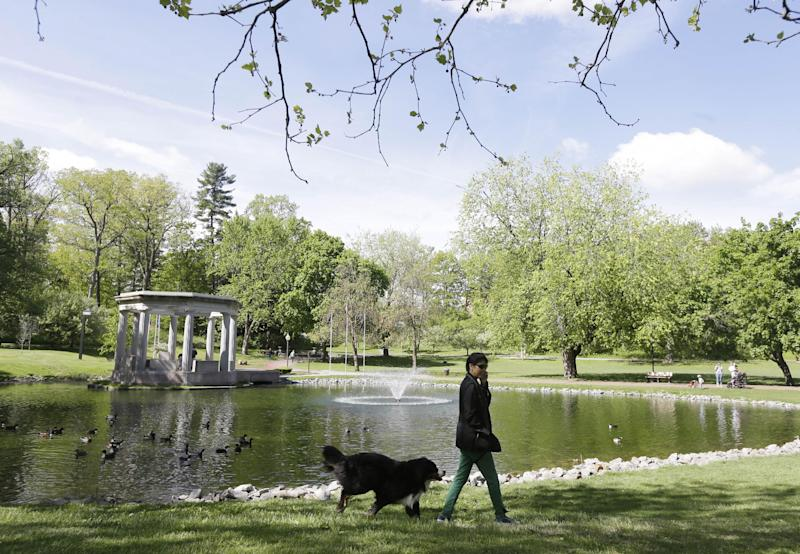 This May 17, 2013 photo shows Nancy Mah, of New York, and her dog Memphis walking in Congress Park in Saratoga Springs, N.Y. Saratoga Springs' racetrack is still going strong as it marks its 150th anniversary this summer, the centerpiece attraction in a town that's also known for mineral springs, Victorian charm and upscale hotels, shops and restaurants. (AP Photo/Mike Groll)