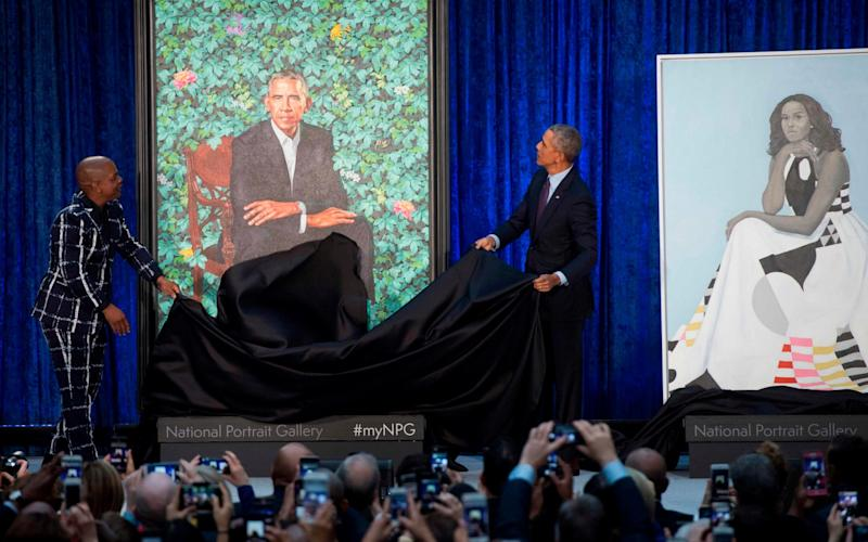 Former US President Barack Obama unveils his portrait alongside the portrait's artist, Kehinde Wiley, at the Smithsonian's National Portrait Gallery in Washington - AFP